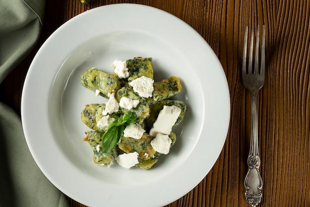 Grüne gnocchi mit basilikum, spinat, pesto-feta-käse in komposition mit grünem tuch und olivenöl.