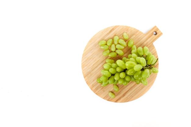 Grüne grapefruits ein hölzernes schneidebrett, flache draufsicht
