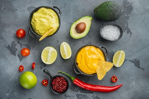 Grüne guacamole und gelbe käse-dip-sauce für traditionelle mexikanische tacos, auf grauem tisch, draufsicht oder flachem lay