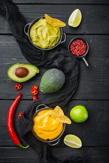 Grüne guacamole und gelbe käse-dip-sauce für traditionelle mexikanische tacos, auf schwarzem holztisch, draufsicht oder flachem lay