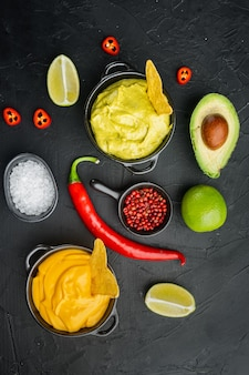 Grüne guacamole und gelbe käse-dip-sauce für traditionelle mexikanische tacos, auf schwarzem tisch, draufsicht oder flachem lay