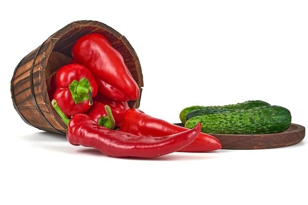 Grüne gurke auf einer holzplatte mit chilis im eimer.