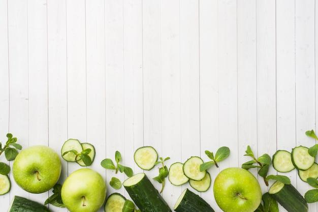 Grüne gurke tadelloses apple auf dem tisch.