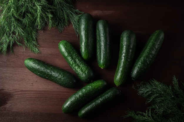 Grüne gurken, dill und petersilie auf einem holztisch