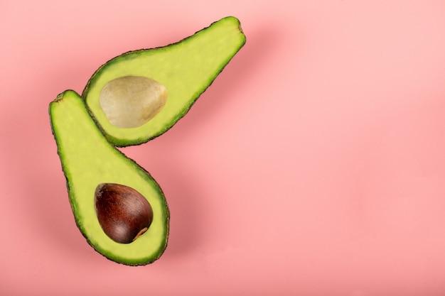 Grüne halbe avocados isoliert auf rosa wand, mit und ohne samen
