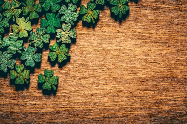 Grüne hölzerne vierblatt-shamrocks auf hölzernem brett