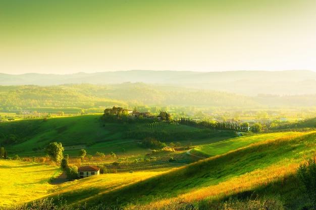 Grüne hügel bei sonnenuntergang in der toskana italien schöne sommerlandschaft felder mit frischem grünem gras