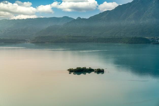 Grüne hügel, umgeben vom meer unter sonnenlicht und bewölktem himmel