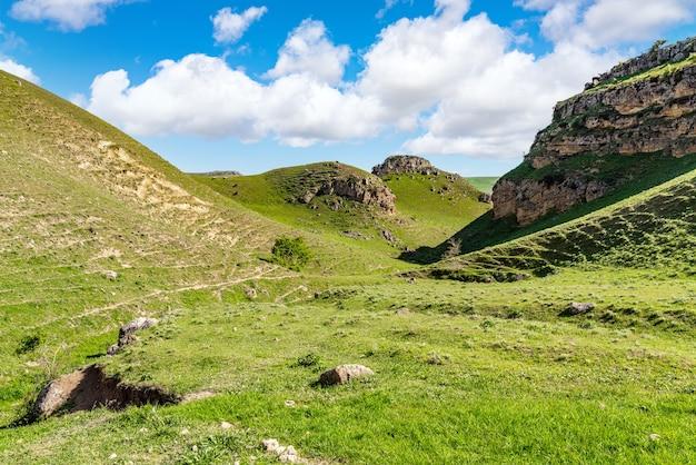 Grüne hügel und felsen mit wolken auf landschaft des blauen himmels