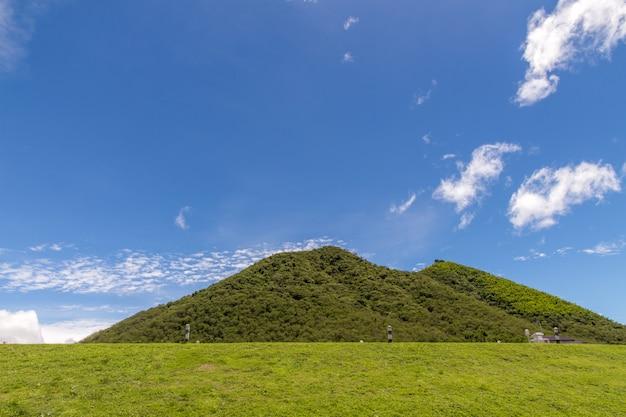 Grüne hügel und zaun üppiges gras, blauer himmel mit weißen wolken