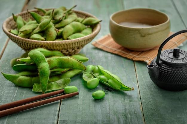 Grüne japanische sojabohne in der hölzernen schüssel auf tabellenholz