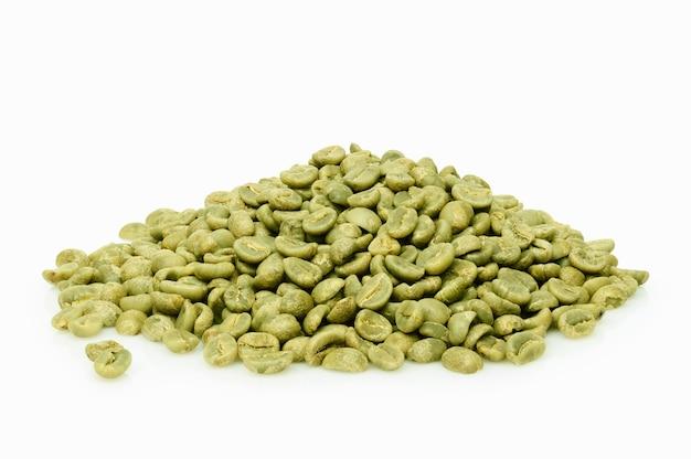 Grüne kaffeebohnen stapeln auf weißem hintergrund