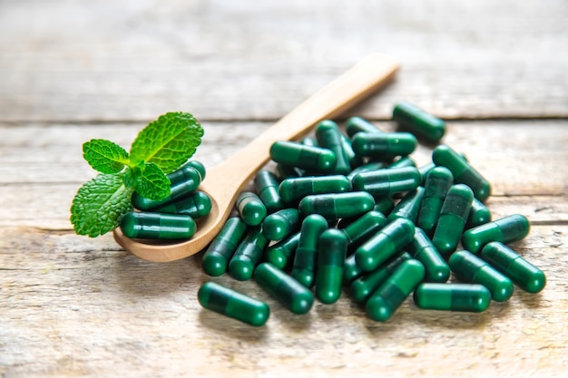 Grüne kapseln, kräutermedikamente, beruhigungsmittel mit minze. selektiver fokus natur