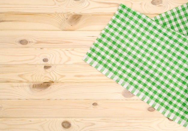 Grüne karierte tischdecke auf holztisch