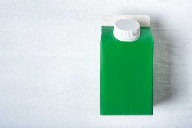 Grüne kartonschachtel oder verpackung der tetra-packung mit kappe.