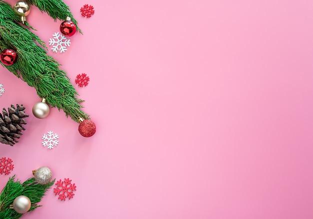 Grüne kiefer, kiefernkegel, schneeflocken, roter weihnachtsverzierungsball auf rosa hintergrund mit kopienraum