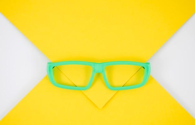 Grüne kinderbrillen auf buntem hintergrund