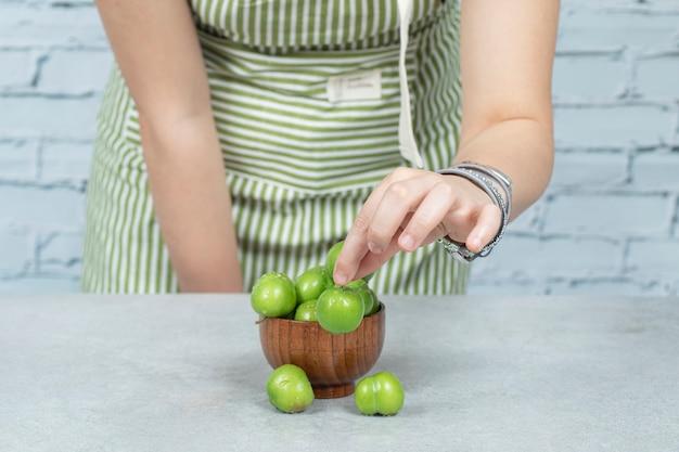 Grüne kirschpflaumen in eine holzschale geben