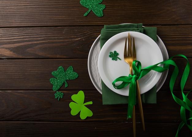 Grüne kleeblätter zum st. patrick's day mit gabel, löffel und serviette