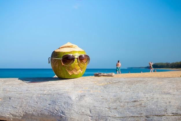 Grüne kokosnuss als halloween-symbol in form eines kürbisses er trägt eine sonnenbrille steht am strand