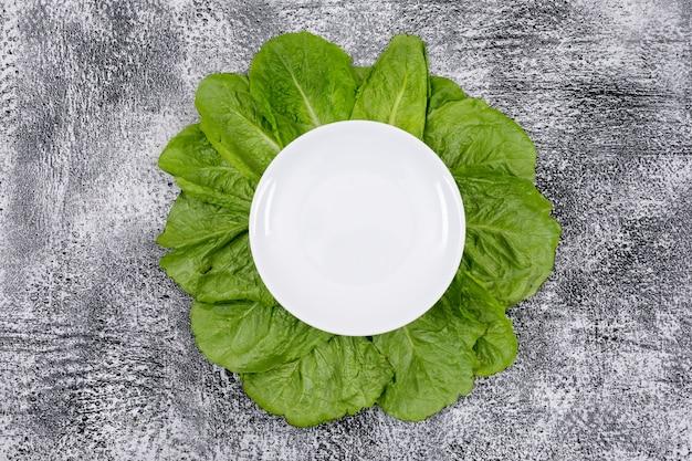 Grüne kopfsalatblätter unter leerer weißer platte