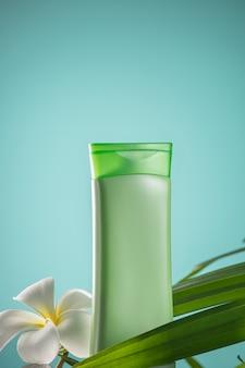 Grüne kosmetikflasche mit frangipani-blüten