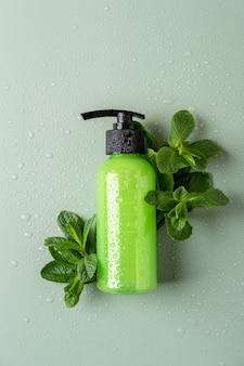 Grüne kosmetikflasche mit spender, frischer minze und wassertropfen. biokosmetik-konzept. kosmetisches containermodell mit platz für text. natürliches hautpflegeprodukt.