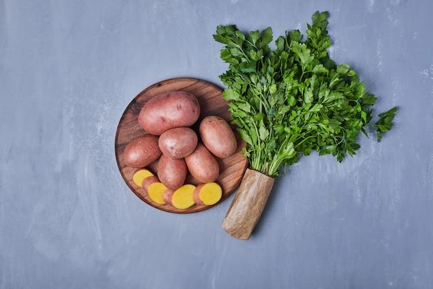 Grüne kräuter mit kartoffeln auf blau