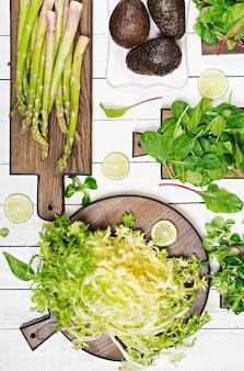 Grüne kräuter, spargel und schwarze avocado auf einer weißen holzoberfläche. draufsicht. flach liegen