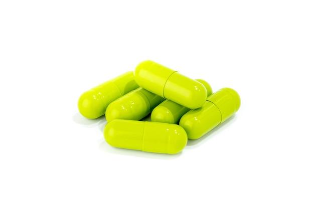 Grüne kräutermedizin-kapseln auf weiß