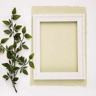 Grüne künstliche blätter nahe dem weißen holzrahmen auf papier gegen weißen hintergrund