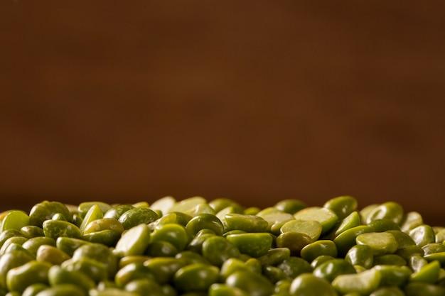 Grüne linsen in der holzschale auf holzhintergrund. essbare rohe hülsenfrüchte der hülsenfruchtfamilie.
