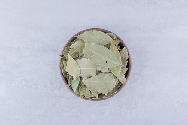 Grüne lorbeerblätter in einer schüssel trocknen. foto in hoher qualität