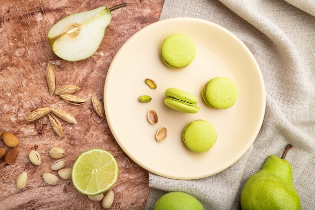 Grüne macarons oder macaroons-kuchen mit tasse kaffee auf einem braunen betonhintergrund und leinentextil. draufsicht, flach liegen,