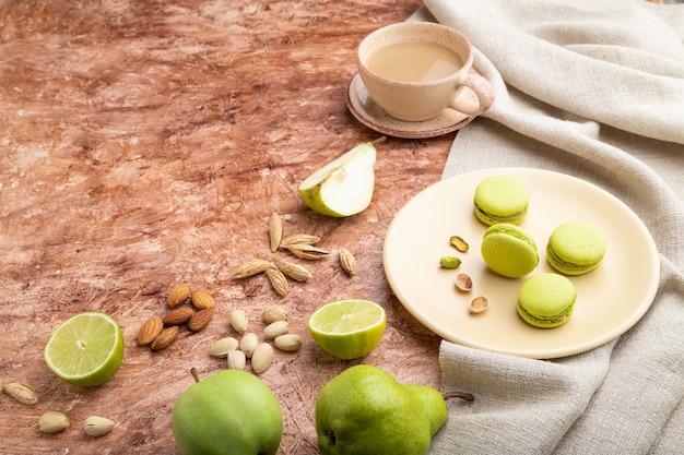 Grüne macarons oder macaroons-kuchen mit tasse kaffee auf einem braunen betonhintergrund und leinentextil. seitenansicht,
