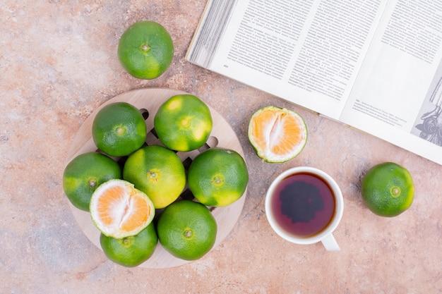 Grüne mandarinen mit einer tasse tee