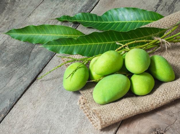 Grüne mango auf holzhintergrund. thailändisches lebensmittelkonzept.