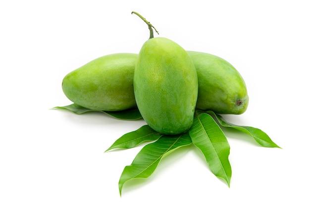 Grüne mangos werden auf mangoblätter gelegt, die auf weißem hintergrund isoliert werden.