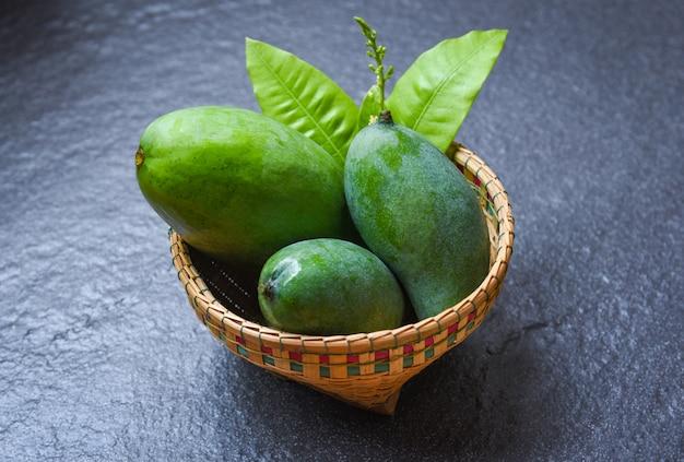 Grüne mangosommerfrucht und grünblätter im korb auf dunkelheit
