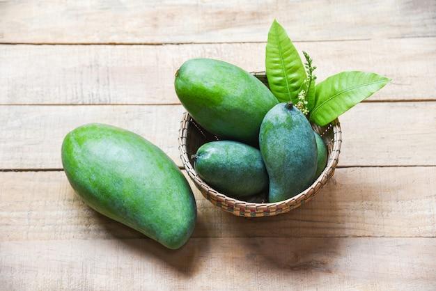Grüne mangosommerfrucht und grünblätter im korb auf holz