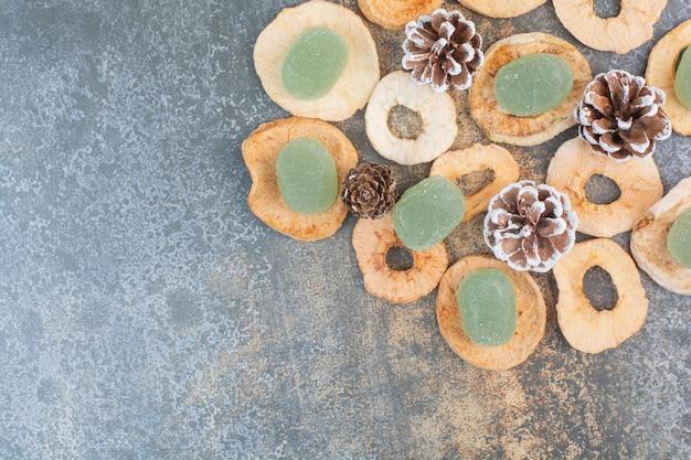 Grüne marmelade mit getrockneten früchten und tannenzapfen auf marmorhintergrund. hochwertiges foto