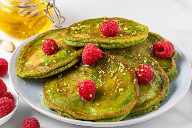 Grüne matcha hausgemachte pfannkuchen mit frischen himbeeren, pistazien und honig auf weiß