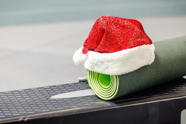 Grüne matte mit weihnachtsmannmütze im fitnessstudio