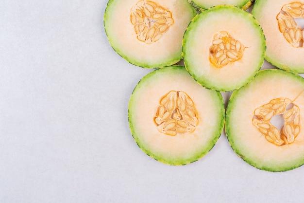 Grüne melonenscheiben auf weißer oberfläche