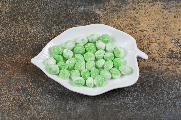 Grüne menthol-bonbons auf blattförmigem teller.