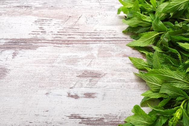 Grüne minzblätter auf holzoberfläche