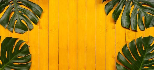 Grüne monstera-blätter auf gelbem holzboden und kopienraum für die gestaltung in ihrem arbeitskonzept.