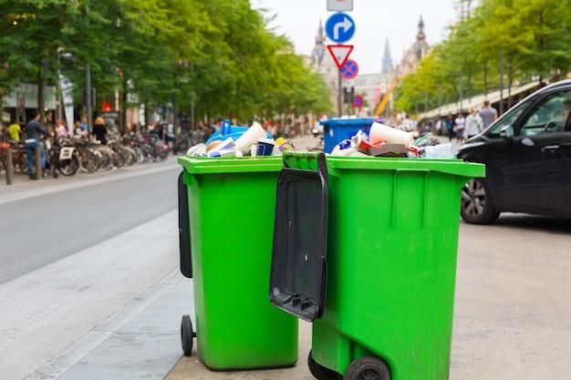 Grüne mülltonne auf bürgersteig, europäische stadt. voller mülleimer auf der straße in europa, niemand, mülleimer, großer plastikbehälter im freien