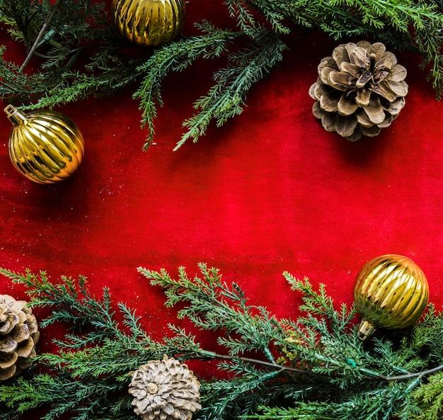 Grüne nadelzweige, haken und ornamentkugeln