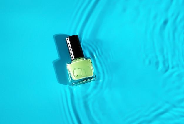 Grüne nagellackflasche im top-schuss des blauen wassers. nagellackflasche in sauberem wasser.